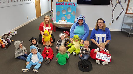 Infants sitting with each other in Halloween costumes