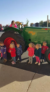 Toddlers standing next to a tractor