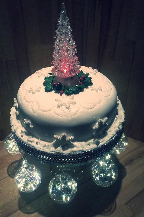 Lit tree and snow Christmas cake