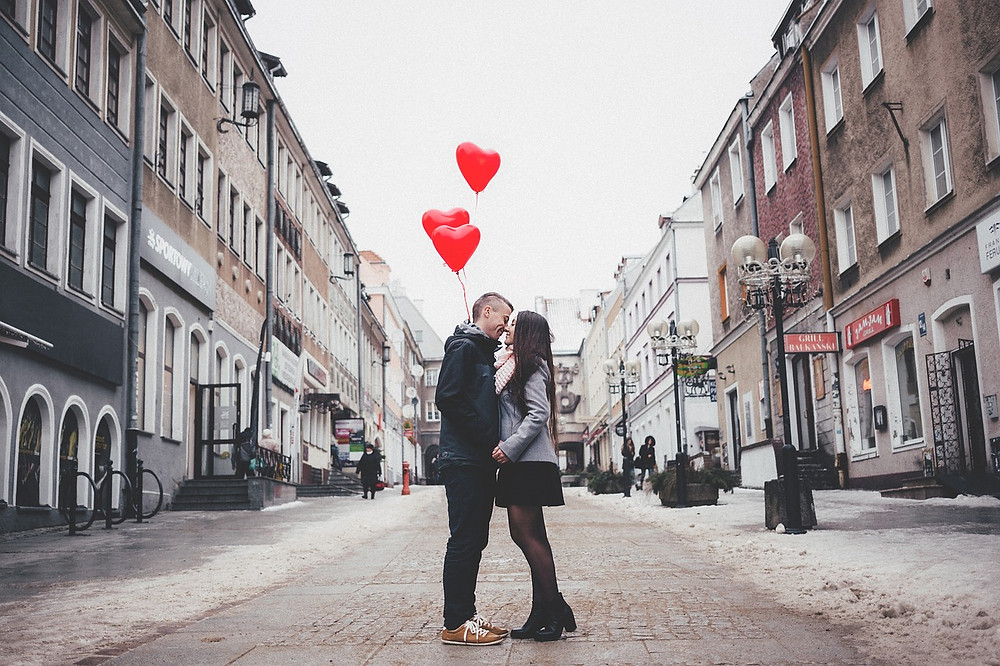 Intimate couple standing in street kissing