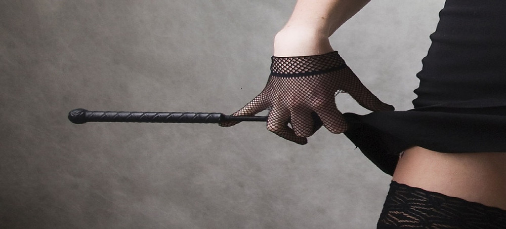 Person wearing fishnet gloves and holding a dominatrix wand