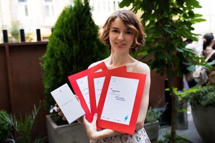 The winner holding her certificates