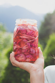 A can of pink-colored pickles in Mikaela's hand