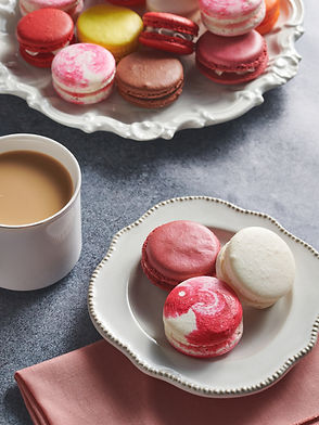 A cup of coffee and plates with macaroons