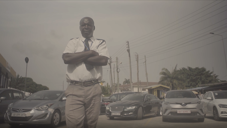 A black male security guard standing with his arms folded