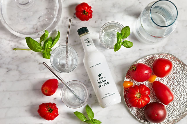 A bottle of No1 Botanicals Basil Water lying on a marble surface with basil leaves tomatoes and glasses of sparling water with metal straws dotted around