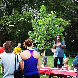 Camilla is talking to audience while at a park, tree is in the background.  She is wearing a grey t-shirt, yoga pants, and wearing sunglasses.  People are standing around and listening.