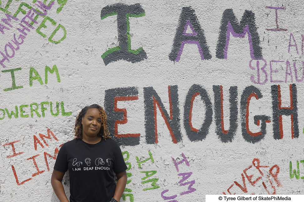 Camilla is standing in front of artwork outside that says I am Enough.  She is wearing a Black t-shirt that has pictures of different hearing aid devices.  Shirts says I am Deaf enough.