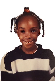 Camilla's second grade school picture.  Camilla is smiling and wearing a black and white sweater.  Wearing a bone achored conduction hearing aid device.