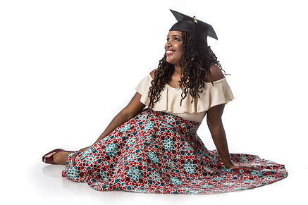 Camilla is sitting looking towards the sky with graduation cap on and smiling.  Wearing a red, light brown, and teal color skirt with light brown color top.