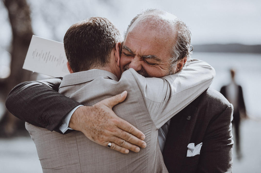 man hugging his son on wedding day