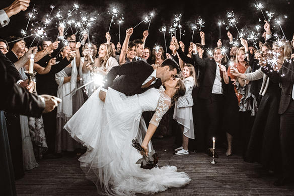 wedding couple kissing around sparklers