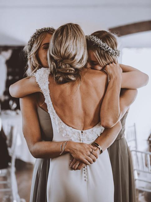 bride hugging bridesmaids