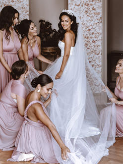 bridesmaids preparing the weddingdress