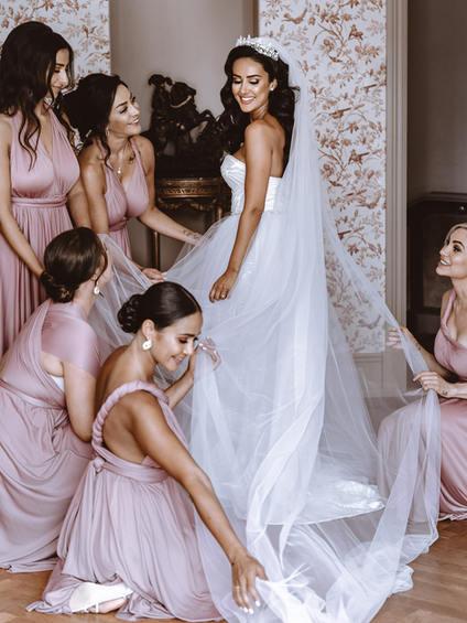 bridesmaids preparing the weddingdress