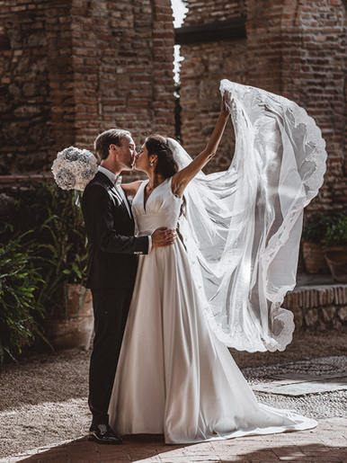 bride kissing husband with weddingdress
