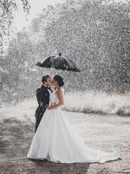 Wedding couple kissing in rain