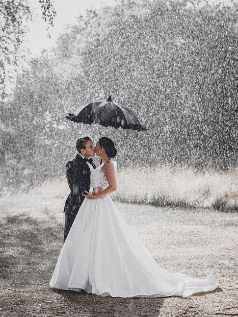 Wedding couple kissing in rain