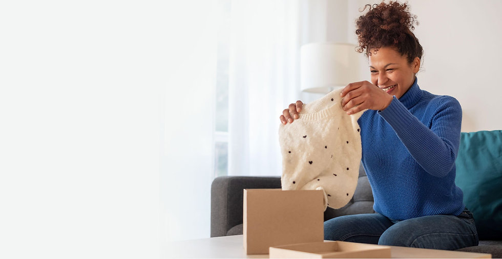 A woman holds a sweater she just purchased online