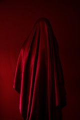 This portrait colour image is toned almost entirely in red and black. A red cloaked figure is stood in front of a red background. We are unable to see who the cloaked figure is or what they are doing. The image feels other-worldly. The red fabric ripples and creates dark toned shadows which contrast against the bright red highlighted areas of the cloak.