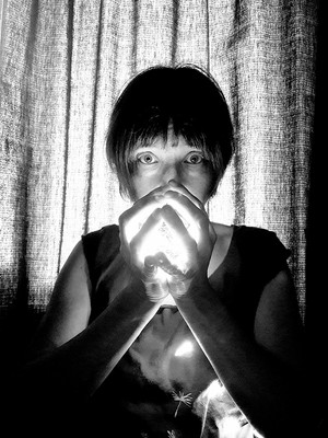 This is a black and white portrait image of a woman from the waist up looking directly at the camera. Her hands are raised to her just beneath her eyes and cupped together. Within her hands appears to be a magical bright light emanating and lighting her face and t-shirt. Behind her is a textured length of fabric. The bottom section of the image is dark in contrast.