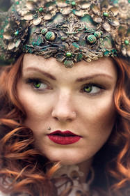 This is a portrait colour image of a woman wearing an intricately decorated headpiece in tones of green and gold. It features swirls of texture and insects. From the headers, ginger curly hair falls to frame the woman's face. She is wearing red lipstick which is striking against the green of the headpiece. Her gaze is to the far left, away from the camera.