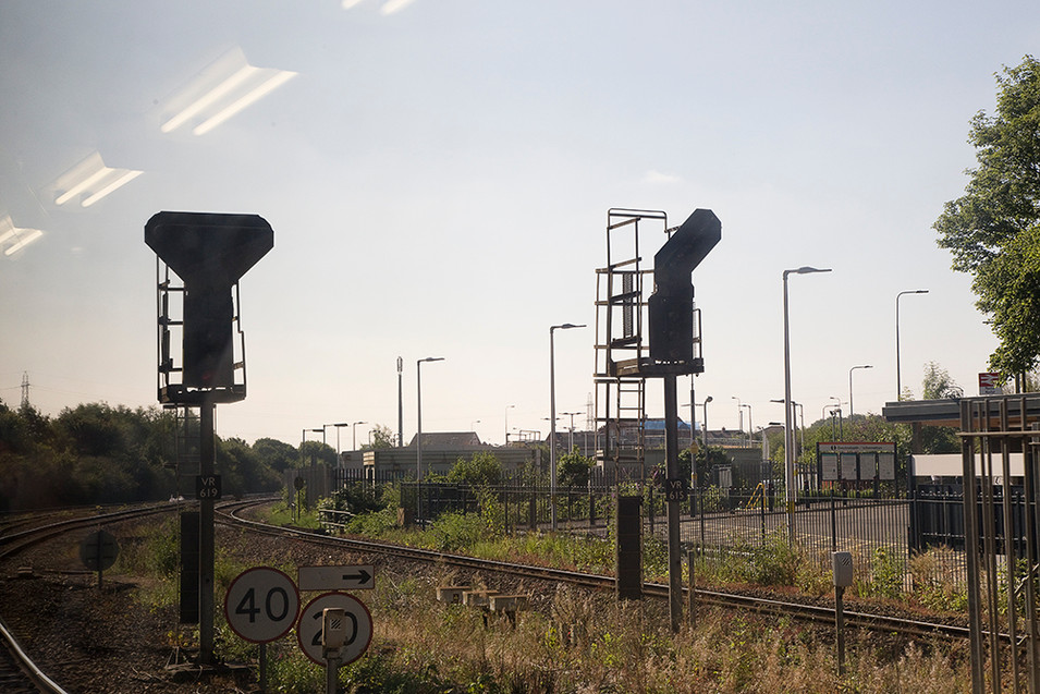 This is a photograph of a train track line and train station. There are numerous tall lamp posts and signs with information for train drivers. There are two large stop and go train traffic signal posts that dominate the image. To the far left of the picture are four bright lights reflected on the window from the inside of the train carriage.