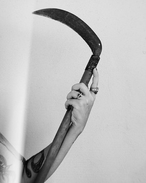 This is a black and white portrait image of a tattooed arm holding a large scythe made of metal and wood. A beam of light strikes the left side of the arm. Around this scene is a plane pale grey wall with lots of lovely negative space.