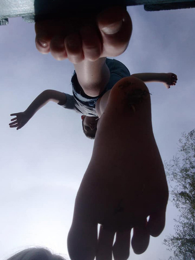 This is a colour image of a young boy standing above the camera looking downwards. The perspective of the photo is from the ground looking upwards. Two bare feet hover above the camera phone, as if the boy was floating in the air. The boy's hands are open and in the air, as if he was trying to balance whilst flying through the blue sky.