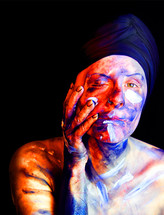 Titled 'Anxiety', this colour portrait image depicts what anxious thoughts and feelings might look like if they could appear externally on the skin. The textured and coloured paint upon the model's face and body creates an agitated appearance.  Anxiety as an invisible force that can govern our every day life, this image seeks to paint a picture of what it feels like. The paint upon the model's skin ranges from white through to red, blue and black. The mode's one hand is raised to her face, pulling at the side of her cheek to create a slight distortion to the way in which the face appears. A black background makes the model the main feature of the image.
