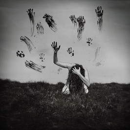This black and white square format self portrait image, titled 'Caged' depicts a girl, on her knees with an arm outstretched and holding on to an invisible force that contains her. Hands prints can be seen around her as though she has tried to break free from this invisible cage. As the image is black and white the scene appears to be almost sculptural. A dark grassy landscape runs across the bottom third of the image with grey skies filling the rest.