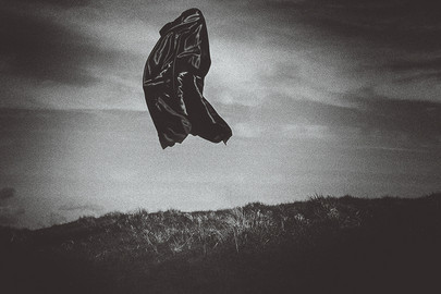 This is a black and white image that appears to be very simple in its design. A dark coloured grassy mountain takes up a third of the bottom part of the image whilst the sky above is in tones of white, grey and almost black with moody clouds strewn across the sky. A floating black figure levitates in the centre-left section of the image. We are unsure of the size of the figure without anything else in the image to create a sense of scale.