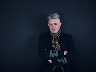 This is a landscape format picture of a man with silver hair stood in front of a dark blu e background. His arms are folded and he is looking to the bottom left side of the image. He is wearing a leopard print scarf and a military style black and grey jacket.