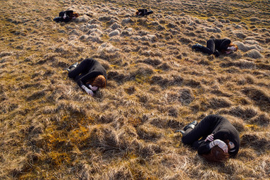 This landscape image made up completely of of orange toned dry grass. Dotted around the landscape are five figures that are all dressed in black jeans and jumpers. Each figure is laying in a foetal position on the floor with their face in their hands or concealed from view by long ginger hair.