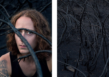 This is two images side by side with a thin white border in between. The image on the right is of a burnt mountainside with tall black curved branches. The image on the left mirrors this with the same curved black branches running across the photo, except a man with jaw length auburn hair is stood in front of the piercing branches. Parts of his face are obscured, but his one eye is visible and is looking directly into the camera in a confrontation manner.