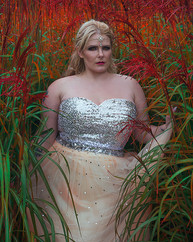 This is a portrait colour image of a woman with long blonde hair wearing a sequinned dress in shades of silver and pale peach. This is a very colourful image shot outdoors. The model is stood on tall green grass which has vibrant red and orange flowers and seeds at the ends. She is looking directly at the camera with her head slightly to the side.