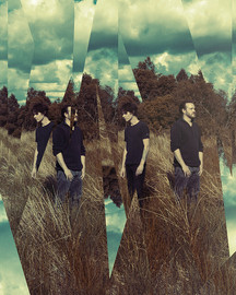 This is a portrait image of the band, Dead End Disco. The photograph is of a field with tall grass and a blue sky above with white fluffy clouds dotted around. Two men are stood in the field, looking away from each other. The image has been manipulated so that it looks like a broken mirror with shards of reflected image cut and copied. Because of this effect, there is two versions of the men stood, each cut out and duplicated. The image has unusual tones of orange and ultra blue, referencing the 1990's musical aesthetic.