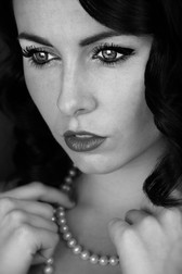This is a portrait black and white image of a woman's face. She has black wavy hair that frames her pale face. She is looking downwards, not engaging with the camera and seeming to appear lost in thought. Her eyes are made up with black eyeliner. She is wearing a pearl necklace, which she is holding on to.