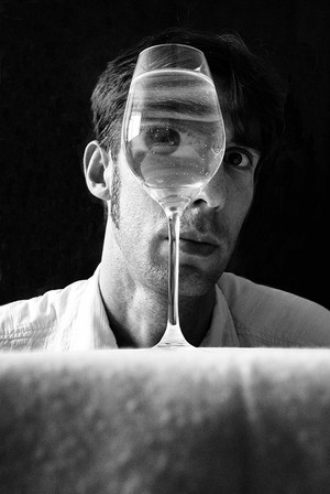 This is a black and white portrait image of a wine glass filled with water. Behind the glass is a man's face. The glass distorts the man's face so that his eye appears to be much larger than the rest of his facial features. The man is wearing a white shirt and the room behind him is black which means the focus is solely on him and this surreal scene.