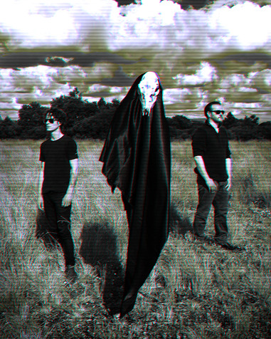 This is a monochromatic portrait image of the band, Dead End Disco. The image is black and white with a slight dirty orange and brown tone. The two band members are stood apart and looking away from each other in a field of tall grass which is surrounded by dark trees in the distant background. Between them floats a black figure with a sheep's skull for a face. The photograph has textured lines across it, as though it was an photo of a TV screen.
