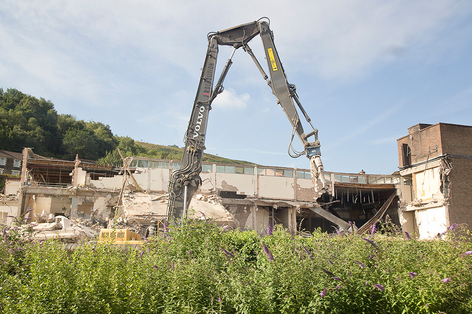 This is a photo of the same scene as the previous image of a building being demolished. In this photograph, there is a large mechanical arm of a demolition digger that pierces the sky. Behind is the ruined building with walls smashed to the ground. A row of green butterfly bushes frame the bottom section of the image. And beyond the building a green mountainside can be seen making the building almost feel out of place and imposed amongst nature.