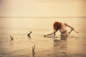 This self portrait image is titled, 'A Drowning.' The image depicts a seascape of calm, still water. Five hands reach from the water upwards, as though trying to grab onto something to pull them up or perhaps pull something down into the depths where they reside. A ginger haired figure is stood, waist deep in the water wearing a pearl coloured dress. Two of the hands reach out from the sea to pull at her hair and arm. The image is orange in toned, making it feel other-worldly and not based in reality.