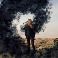 A woman dressed all in black is boldly stood in the centre of this square image with a grassy landscape behind her that rises up toward a pale pink and blue toned sky that takes up two thirds of the image. A large circular plume of smoke seems to be emanating from the woman's back and around the image. The defiant look on the woman's face states that she is not scared of the black mass around her and instead is looking out at the viewer.