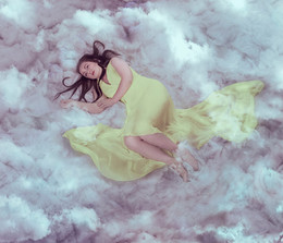 This is a colour image of a woman with long flowing dark brown hair laying in a bed of clouds. She is wearing a pale yellow dress that ripples out around her. She has a vacant look upon her face, as though day dreaming. Small whips of cloud circle around her ankles and arms. The image has a pale blue tone to it.