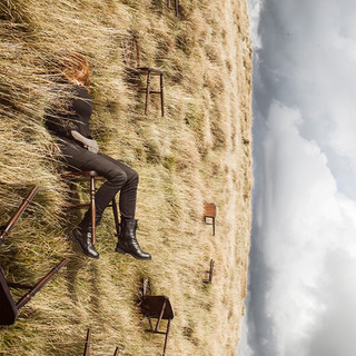 This is a square image, of a grassy mountain top with a moody grey cloudy sky behind. The image however has been rotated 90 degrees so that the landscape is on it's side. A woman wearing black jeans and jumper is sitting on a chair in the landscape, again turned at a 90 degree angle. Her face is covered by long hair swept up in the wind. Around her lay other wooden brown chairs, fallen down and laying on their sides.