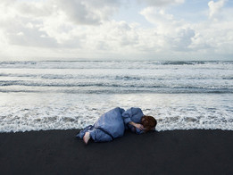 This is a landscape image of a beach scene. Waves are crashing in a stormy sea, crawling up the dark sands of the beach. On the sand lays a woman in a greyish blue dress. She is curled up in a foetal position with her hand covering her face. The tide is around her and a wave is about to crash  into her back. The sky above the sea appears to be sunny with clouds, as if a storm has just passed and the weather is brightening up.