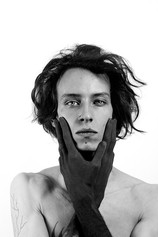 This is a black and white portrait shot of a man stood in front of a white background. It is cropped from his chest upwards. The model is topless with his hands painted black as they gently hold each side of his face. He is also looking directly at the camera.