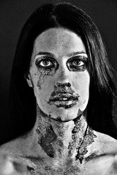 This is a black and white grainy portrait image of a woman with long dark straight hair looking directly at the camera. Her skin has dark freckles speckled on it that match the texture of her unusual make-up. Around her eyes, nose and nose and over sections of her neck are glittery patches as though they were peeling away to reveal her skin underneath.