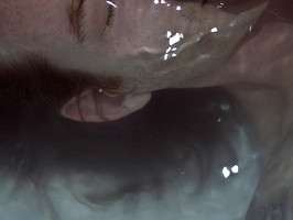 This is a landscape image of a man with jaw length hair submerged in pale blue water. The close up crop of the photo feels intrusive and with only a thin slither of the model's face shown, it is unclear as to why he is underwater. White flecks of water reflect a light source from above.