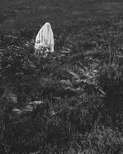 This is a black and white photograph of a mountainside covered in heather and ferns. Amongst the bracken is a figure covered in a white cloth in the top left side of the photograph. Their head, torso and waist pop over the tall ferns in a ghostly appearance. They are completely alien to the landscape but their distance from the camera somehow makes it feel as though they belong.
